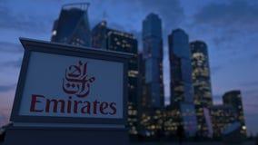 Straatsignage raad met de Luchtvaartlijnembleem van Emiraten in de avond Vage bedrijfsdistrictswolkenkrabbers backgroun Royalty-vrije Stock Afbeeldingen