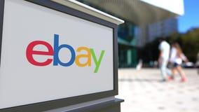 Straatsignage raad met eBay N.v. embleem Vage bureaucentrum en het lopen mensenachtergrond Het redactie 3D teruggeven Royalty-vrije Stock Fotografie