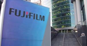 Straatsignage raad met Fujifilm-embleem De moderne wolkenkrabber van het bureaucentrum en tredenachtergrond Het redactie 3D terug Royalty-vrije Stock Foto's