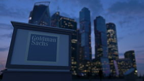 Straatsignage raad met Goldman Sachs Group, N.v. embleem in de avond Vage bedrijfsdistrictswolkenkrabber royalty-vrije stock foto's