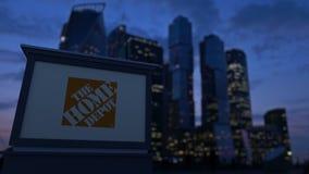 Straatsignage raad met het Home Depot-embleem in de avond De vage achtergrond van bedrijfsdistrictswolkenkrabbers Royalty-vrije Stock Afbeeldingen
