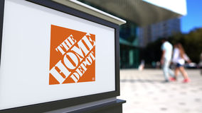 Straatsignage raad met het Home Depot-embleem Vage bureaucentrum en het lopen mensenachtergrond Redactie 3D Royalty-vrije Stock Foto
