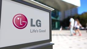 Straatsignage raad met LG-Bedrijfsembleem Vage bureaucentrum en het lopen mensenachtergrond Redactie 3D Royalty-vrije Stock Afbeelding