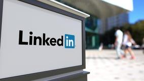 Straatsignage raad met LinkedIn-embleem Vage bureaucentrum en het lopen mensenachtergrond Het redactie 3D teruggeven Royalty-vrije Stock Foto
