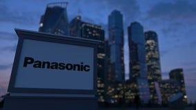Straatsignage raad met Panasonic-Bedrijfsembleem in de avond Vage bedrijfsdistrictswolkenkrabbers backgroun Stock Afbeeldingen
