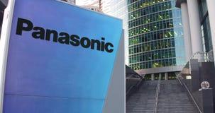 Straatsignage raad met Panasonic-Bedrijfsembleem De moderne wolkenkrabber van het bureaucentrum en tredenachtergrond redactie Stock Foto's