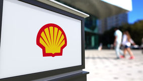 Straatsignage raad met Shell Oil Company-embleem Vage bureaucentrum en het lopen mensenachtergrond Redactie 3D Royalty-vrije Stock Afbeeldingen