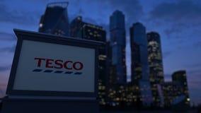 Straatsignage raad met Tesco-embleem in de avond De vage achtergrond van bedrijfsdistrictswolkenkrabbers Redactie 3D royalty-vrije stock foto's
