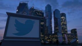 Straatsignage raad met Twitter, N.v. embleem in de avond De vage achtergrond van bedrijfsdistrictswolkenkrabbers Editoria Stock Afbeelding