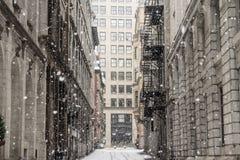 Straatsteeg van oud-Montreal in de winter onder een sneeuwonweer met een moderne wolkenkrabber op de achtergrond stock foto's
