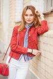 Straatstijl van modieuze jonge vrouw in rood jasje Royalty-vrije Stock Foto's