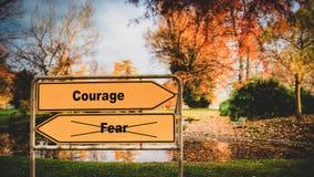 Straatteken aan Moed tegenover Vrees stock afbeeldingen