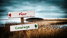 Straatteken aan Moed tegenover Vrees stock foto