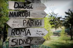 Straattekens in het natuurreservaat die op richtingen wijzen aan verschillende plaatsen van de wereld Groene installaties op de a stock afbeeldingen