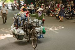 Straatverkoper die haar fietshoogtepunt van goederen op bezige straat duwen royalty-vrije stock fotografie