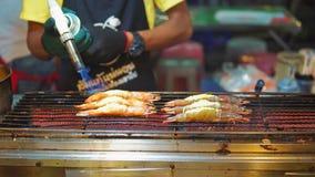 Straatvoedsel Azië, traditionele Aziatische schotels zeevruchtengarnalen op de grill, de koktoost hun brander De markt van het na stock video