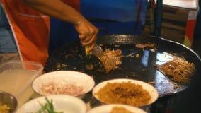 Straatvoedsel: de Thaise mens kookt bij de markt van het nachtvoedsel in Pattaya, Thailand stock video