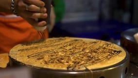 Straatvoedsel: De Thaise mens maakt pannekoeken met bananen en chocolade bij de markt van het nachtvoedsel stock footage