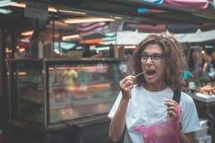 Straatvoedsel in Kuala Lumpur, Maleisië Reizende vrouw die vraatzuchtig gehakt fruit van lokale marktverkoper eten Gestemd beeld, Stock Fotografie