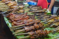 Straatvoedsel in Luang Prabang, Laos De heerlijke verkopende stokken van de voedselbox van geroosterd vlees aan toeristen Aziatis stock fotografie
