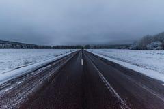 Straatweg met sneeuwgebieden aan beide kanten Stock Afbeelding