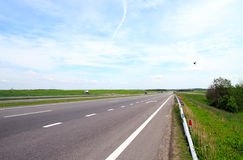 Strada. Motorway, with cars going on it, a grass and the blue sky Royalty Free Stock Photo