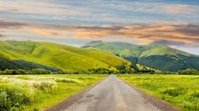 Strada abbandonata attraverso i prati in montagna ad alba Immagine Stock Libera da Diritti