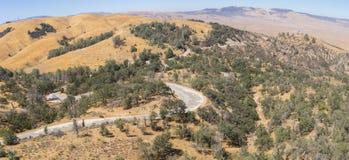Strada abbandonata attraverso il terreno boscoso di California fotografia stock