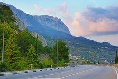 Strada al fianco di una montagna con la vista della scogliera e delle nuvole Fotografia Stock