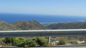 Strada al paesino di montagna Krasi su Creta /Greece Guidando lungo una strada con la vista sopra la baia di Malia stock footage