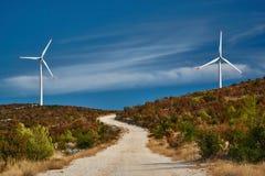 Strada al parco eolico nelle montagne Immagini Stock Libere da Diritti