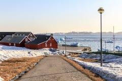 Strada al vecchio porto con gli iceberg in un fiordo immagini stock