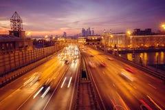 Strada alla notte con le luci da molte automobili sui precedenti della metropoli immagini stock libere da diritti