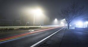 Strada alla notte con nebbia ed esposizione lunga dell'automobile Immagine Stock Libera da Diritti