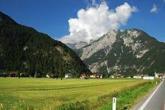 Strada in alpi con i picchi di montagna Immagine Stock Libera da Diritti
