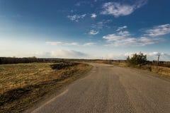 Strada asfaltata attraverso i campi Avanti giri a sinistra Immagine Stock Libera da Diritti