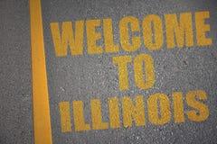 strada asfaltata con il benvenuto del testo ad Illinois vicino alla linea gialla Fotografia Stock Libera da Diritti