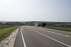 Strada asfaltata con le marcature bianche che passano attraverso la campagna collinosa Fotografia Stock Libera da Diritti