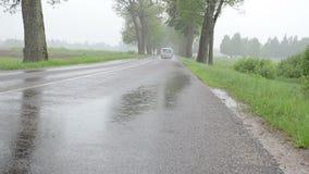Strada asfaltata dell'automobile della pioggia stock footage