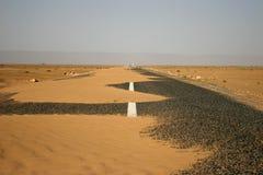 Strada asfaltata nera in pieno della sabbia Fotografia Stock