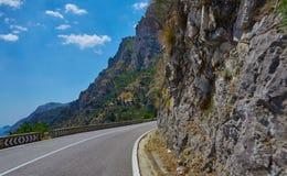 Strada asfaltata Paesaggio variopinto con la bella strada della montagna con un asfalto perfetto Alte rocce, cielo blu ad alba de Fotografia Stock