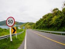Strada asfaltata sulla collina con l'isola del mare del bordo del segno di velocità di limite a phuket Tailandia Immagini Stock Libere da Diritti