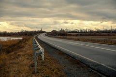 Strada asfaltata vuota con vicino al lago con il cielo nuvoloso alla luce di sera Immagine Stock Libera da Diritti