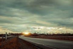 Strada asfaltata vuota con vicino al lago con il cielo nuvoloso alla luce di sera Fotografie Stock