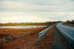 Strada asfaltata vuota con vicino al lago con il cielo nuvoloso alla luce di sera Immagini Stock Libere da Diritti
