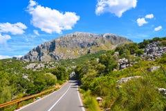 Strada asfaltata vuota ed alta montagna rocciosa Immagini Stock