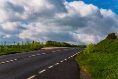 Strada asfaltata vuota, una spalla verde, un'allerta sopra l'oceano, Immagine Stock Libera da Diritti