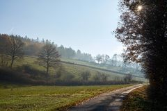 Strada attraverso i campi, il mezzogiorno e la foschia fotografia stock