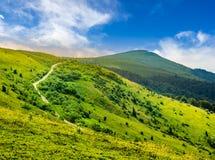 Strada attraverso il pendio di collina in alte montagne ad alba Immagini Stock