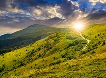 Strada attraverso il pendio di collina in alte montagne al tramonto Fotografia Stock